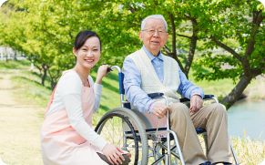 Old man in a wheelchair and his caregiver